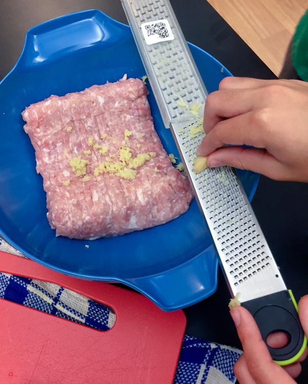 Kids preparing chicken filling for dumplings on eatlivetravelwrite.com