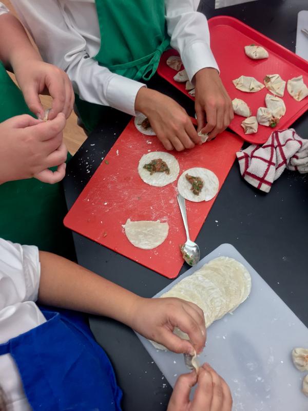 Kids busy folding dumplings on eatlivetravelwrite.com