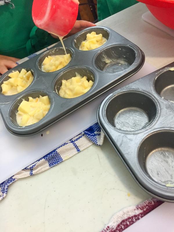 Kids Making Dorie Greenspan custardy apple squares in muffin tins on eatlivetravelwrite.com