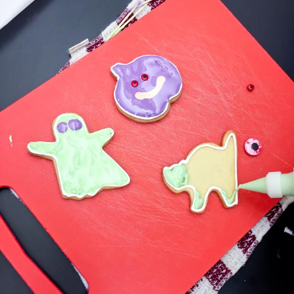 Kids decorating cookies for Halloween on eatlivetravelwrite.com