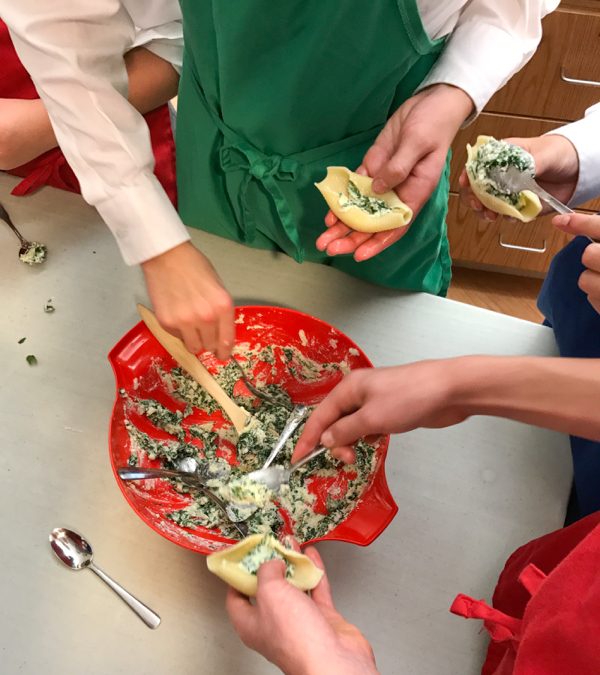Kids filling pasta shells with spinach and ricotta with Emily Richards on eatlivetravelwrite.com
