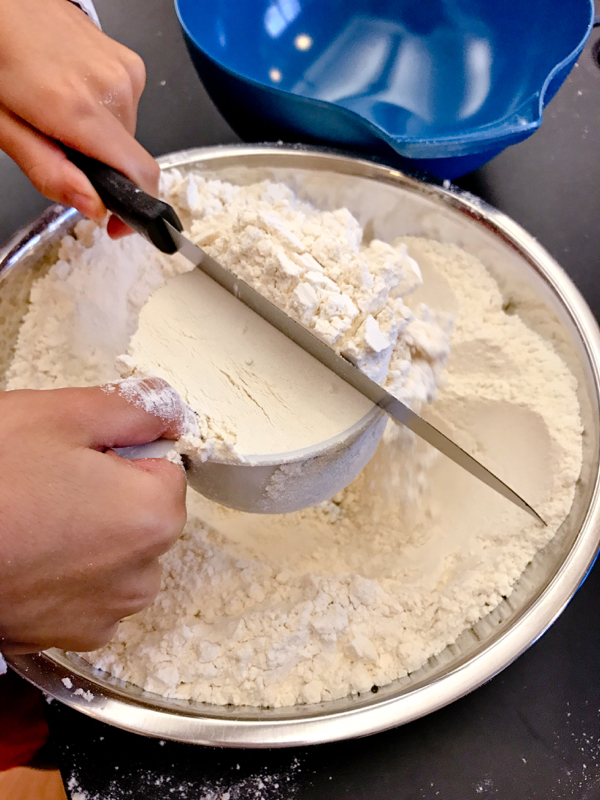 Kids measuring flour to make choux pastry on eatlivetravelwrite.com