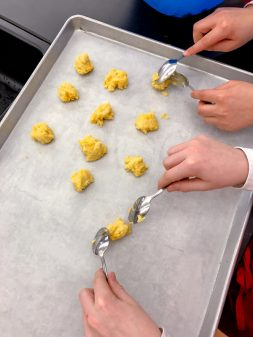 Kids scooping choux pastry to make gougeres on eatlivetravelwrite.com