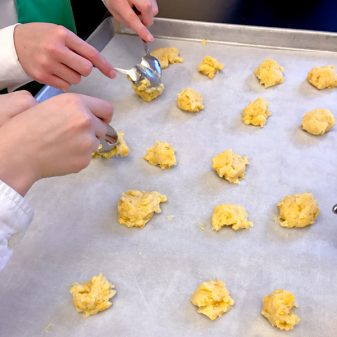 Kids scooping choux pastry with spoons to make gougeres on eatlivetravelwrite.com