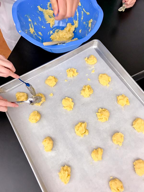 Kids spooning choux pastry to make gougeres on eatlivetravelwrite.com