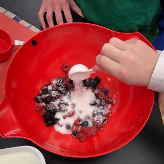 Kids making berry filling for galette on eatlivetravelwrite.com