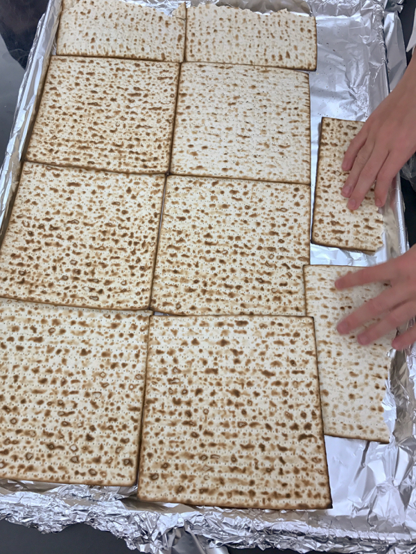 Kids laying out matzoh for David Lebovitz Chocolate-Covered Caramelized Matzoh Crunch