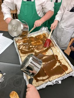 Kids spreading caramel for David Lebovitz Chocolate-Covered Caramelized Matzoh Crunch