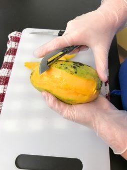 Kids peeling mangoes for hot sauce on eatlivetravelwrite.com