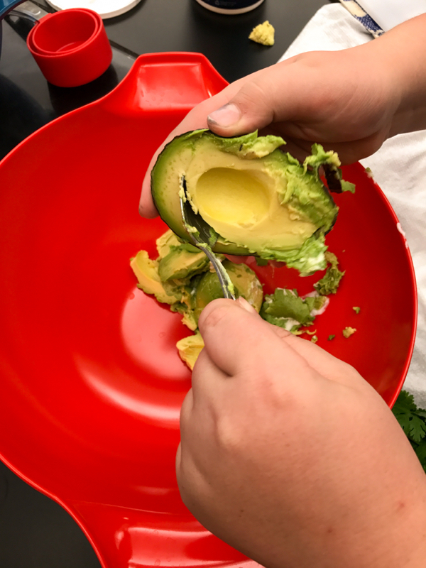 Scooping avocadoes for Joanne Lusted Layered Nacho Dip on eatlivetravelwrite.com