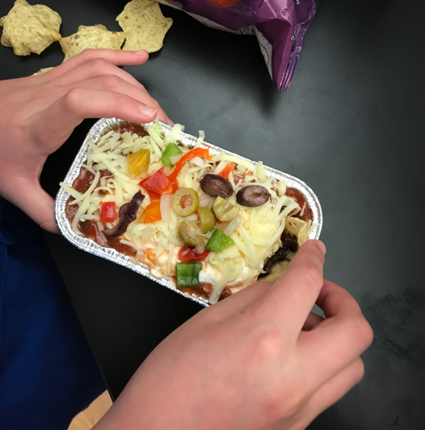 Kids digging into Joanne Lusted Layered Nacho Dip on eatlivetravelwrite.com