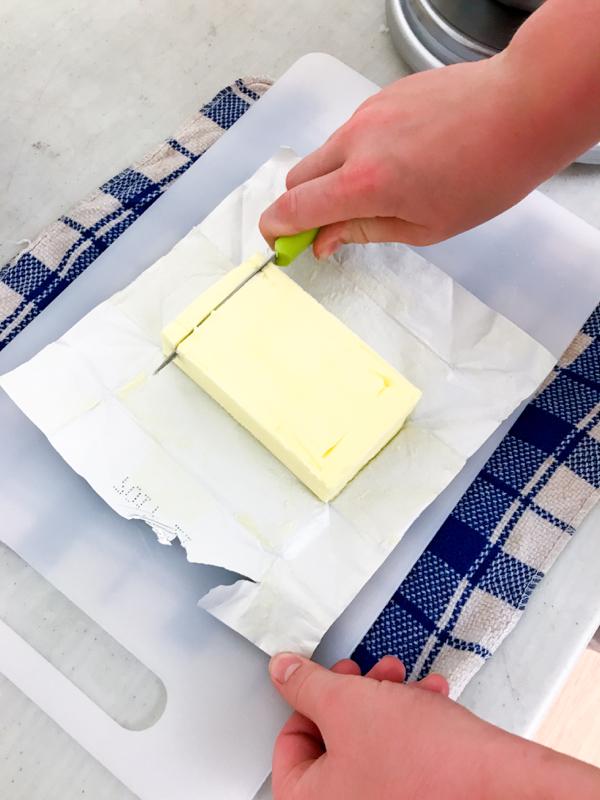 Kids measuring butter for caramel spread on eatlivetravelwrite.com