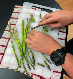 Kids chop asparagus for Jamie Oliver Easy Rustic Gnocchi on eatlivetravelwrite.com
