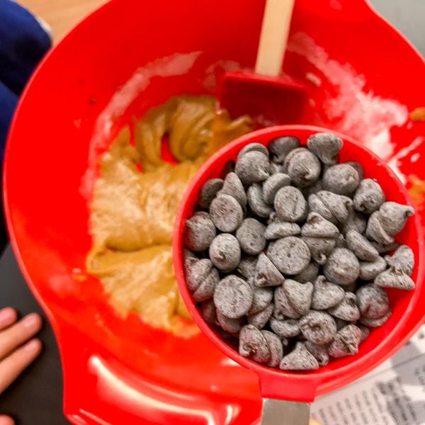 Adding chocolate chips to blondie mixture on eatlivetravelwrite.com
