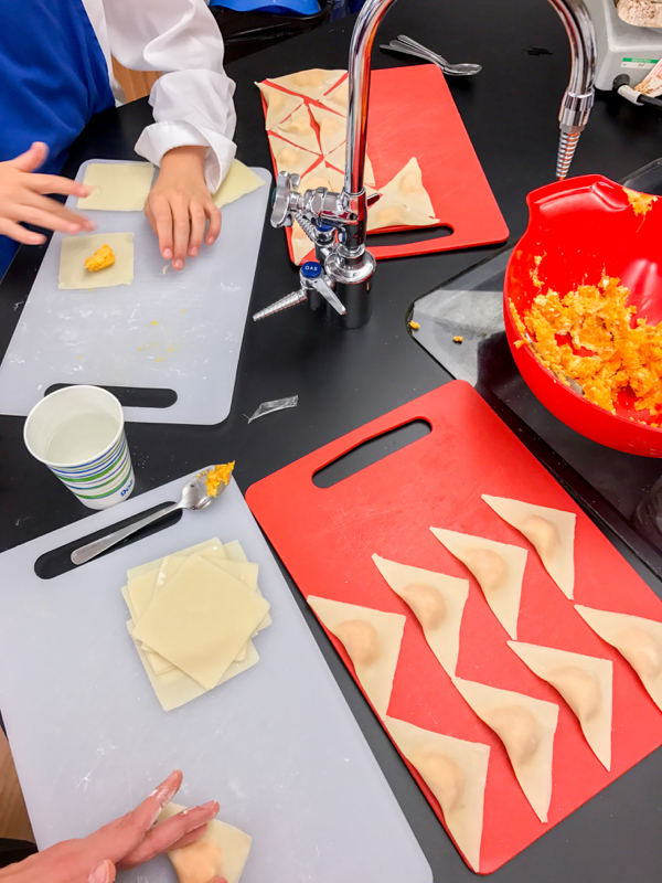 Kids working with wonton wrappers to make ravioli on eatlivetravewrite.com