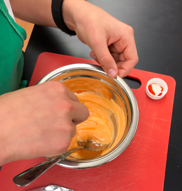 Mixing orange icing with Adell Shneer on eatlivetravelwrite.com