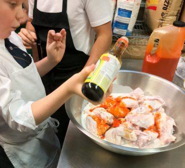 Kids adding fish sauce to chicken marinade at Lisa Maris on eatlivetravelwrite.com