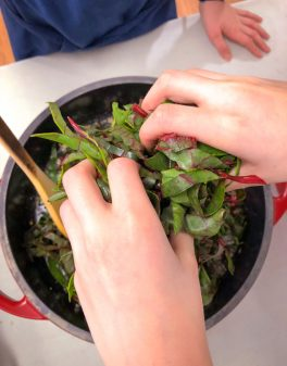Kids adding chard to frying pan for Orecchiette Pasta with Chard from Bringing it Home on eatlivetravelwrite.com