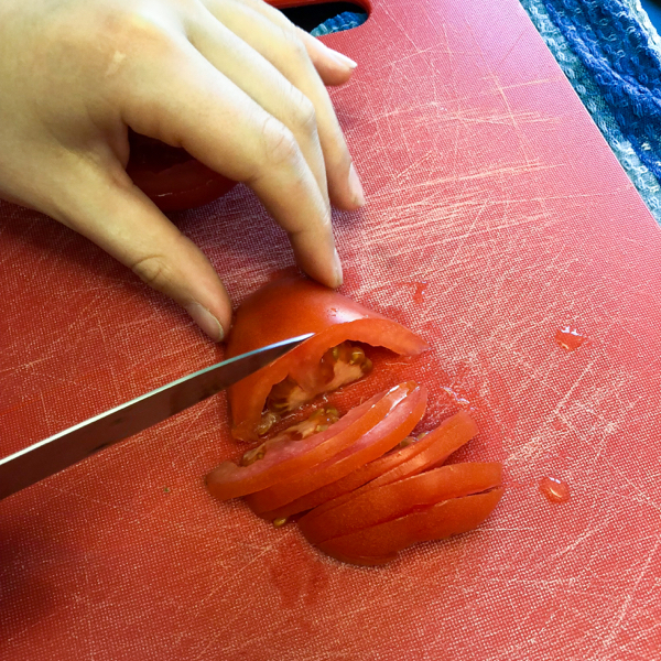 Kids slicing tomatoes for Earls Restaurant tortilla soup on eatlivetravelwrite.com
