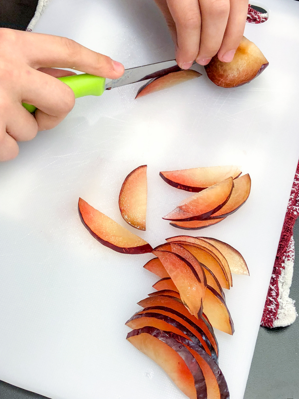 Kids slicing plums to make Caramelized Plum Tartlets from Clotilde Dusoulier Tasting Paris on eatlivetravelwrite.com