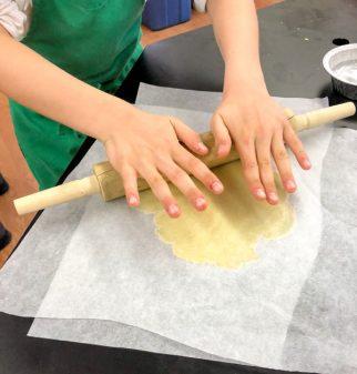 Kids rolling tart dough in parchment for Caramelized Plum Tart from Clotilde Dusoulier Tasting Paris on eatlivetravelwrite.com