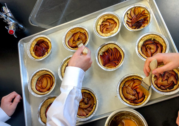 Kids glazing caramelized plum tarts from Clotilde Dusoulier Tasting Paris on eatlivetravelwrite.com
