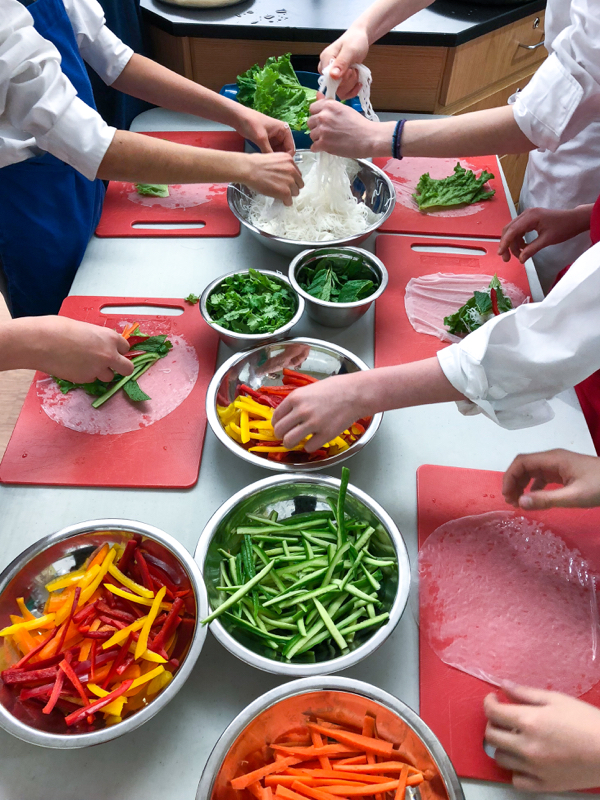Kids making Rainbow Rice Paper Rolls from Vegetarian Vietnam on eatlivetravelwrite.com
