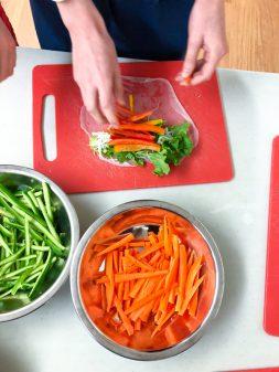 Kids assembling Rainbow Rice Paper Rolls from Vegetarian Vietnam on eatlivetravelwrite.com