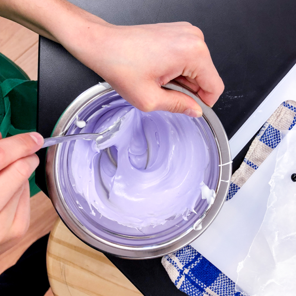 Mixing purple frosting for decorating cookies with Adell Shneer on eatlivetravelwrite.com