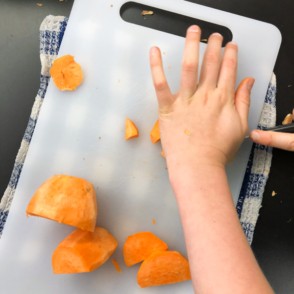 Kids chopping sweet potatoes for Jamie Oliver veggie chili on eatlivetravelwrite.com