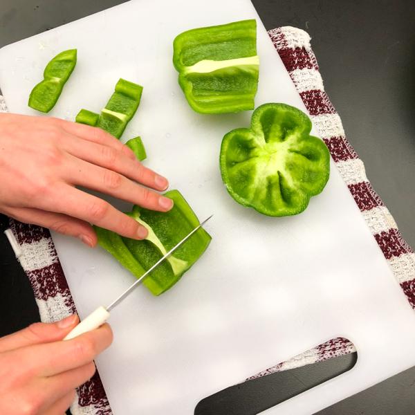 Kids chopping green peppers for Jamie Oliver veggie chili on eatlivetravelwrite.com