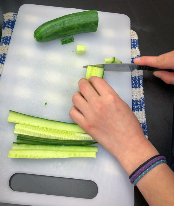 Kids chop cucumbers to make Persian watermelon salad on eatlivetravelwrite.com