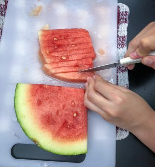 Kids slicing watermelon to make Persian watermelon salad on eatlivetravelwrite.com