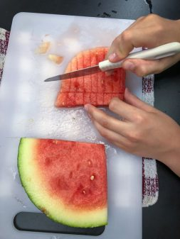 Kids cubing watermelon to make Persian watermelon salad on eatlivetravelwrite.com