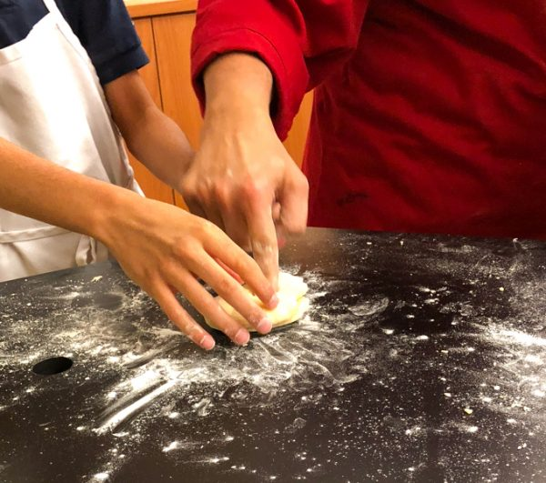 Kids testing readiness of dough for pasta from scratch wth Emily Richards on eatlivetravelwrite.com