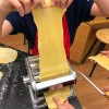 Kids using a pasta machine for pasta from scratch wth Emily Richards on eatlivetravelwrite.com