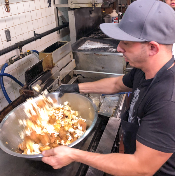 Matt Basile tossing popcorn chicken and waffle bits from Brunch Life at Lisa Marie with Matt Basile on eatlivetravelwrite.com