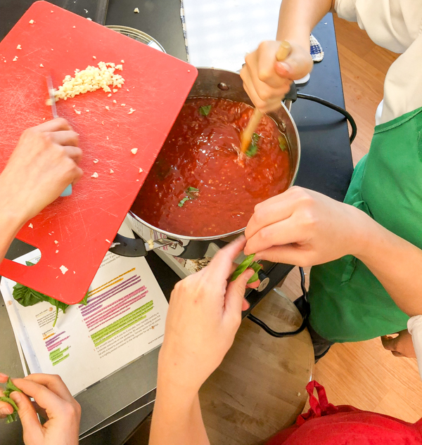 Adding garlic to the tomato sauce for Marble-size Meatballs with Quick and Easy Tomato Sauce from New Favorites for New Cooks on eatlivetravelwrite.com