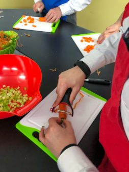 Kids peeling carrots for chicken noodle soup from Oven to Table Cookbook on eatlietravelwrite.com