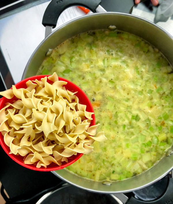 Adding noodles to Chicken Noodle Soup from Oven to Table Cookbook on eatlietravelwrite.com