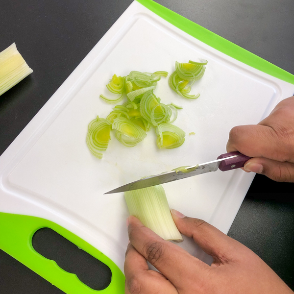 Kids slicing leeks to make Crispy Vegetable Cakes from In the French kitchen with kids on eatlivetravelwrite.com