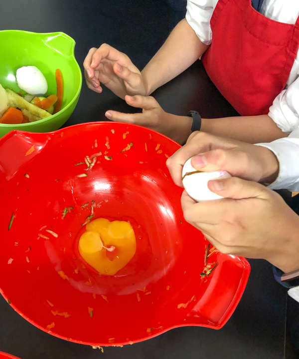 Kids cracking eggs to make Crispy Vegetable Cakes from In the French kitchen with kids on eatlivetravelwrite.com