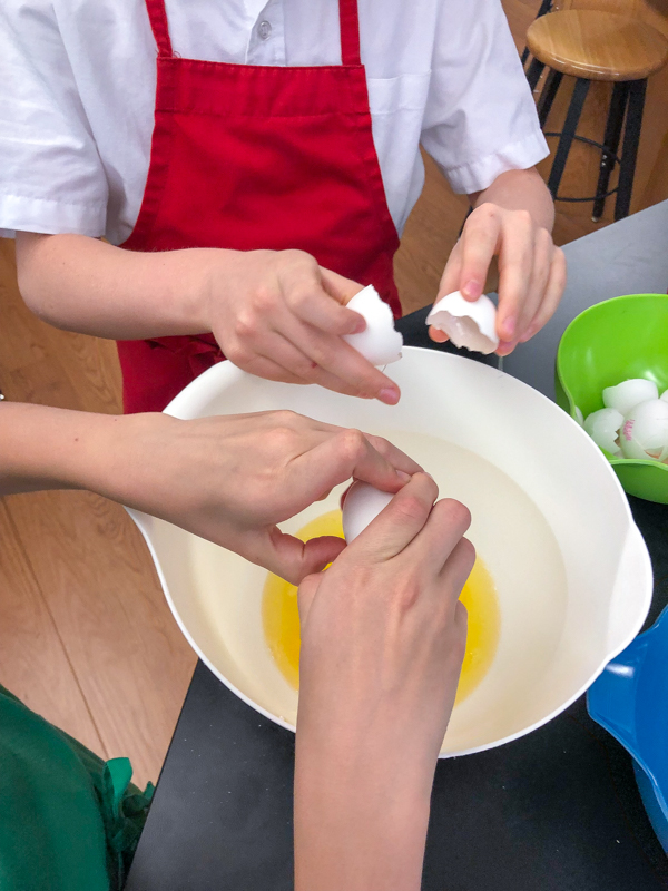 Kids cracking eggs for Bacon spinach and spaghetti frittata from Weekday Suppers by Emily Richards on eatlivetravelwrite.com