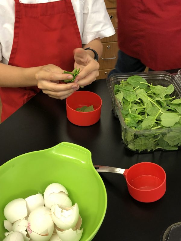 Measuring spinach for Bacon spinach and spaghetti frittata from Weekday Suppers by Emily Richards on eatlivetravelwrite.com