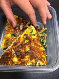 Reaching for the bacon on the Bacon spinach and spaghetti frittata from Weekday Suppers by Emily Richards on eatlivetravelwrite.com