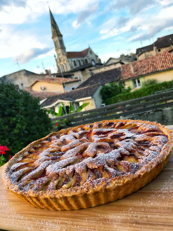 Nérac in the background of a Plum and almond cream tart on eatlivetravelwrite.com
