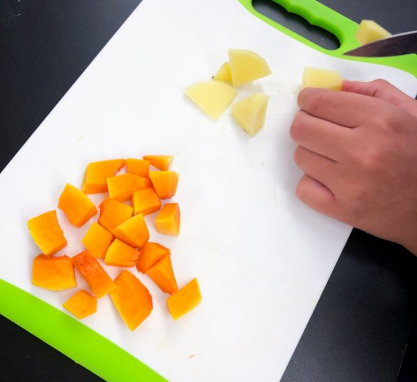 Kids chopping vegetables for Jamie Oliver's Squash Gnocchi from #jamiesveg on eatlivetravelwrite.com