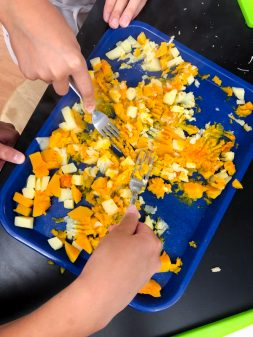 Kids mashing squash and potatoes for Jamie Oliver's Squash Gnocchi from #jamiesveg on eatlivetravelwrite.com