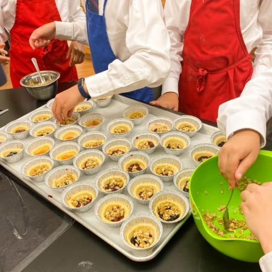 Kids adding crumble to jam in tart shells to make mini jam crumble tarts on eatlivetravelwrite.com