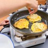 Adding cheese to pan fried Cheesy Corn Cakes with Arugula with Afrim Pristine from Cheese Boutique on eatlivetravelwrite.com
